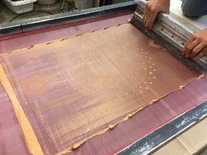 Mit dem so genannten Rakel zieht man die Farbe unter Druck über das Sieb. Durch den Druck des Rakel presst sich die Farbe durch das Muster und wird auf den Stoff übertragen.