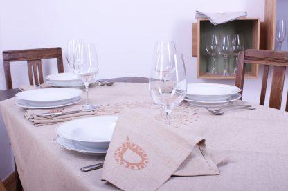 Das Produktfoto zeigt, dass auch eine quadratische Tischdecke auf einem rechteckigen Tisch grandios aussehen kann. Die Tischdecke wurde dafür diagonal auf den Tisch gelegt. Sie misst 120 mal 120 Zentimeter. Zu der sandfarbenen Tischdecke mit handbedrucktem Muster werden passende Stoffservietten präsentiert.