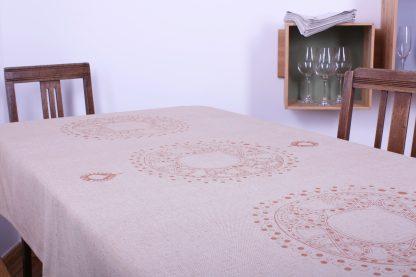 Die sandfarbene Tischdecke in 180 mal 120 Zentimeter eignet sich perfekt für einen mittelgroßen Tisch. Der schöne Sandton des Stoffes wird mit einem handbedruckten Motiv in Bronze veredelt. Mittig befindet sich ein großer, in sich gemusterter Kreis. Links und rechts wiederholt sich das Ornament. Der mittlere Kreis ist oben und unten von zwei kleinen Tropfen flankiert. Das Tischtuch ist ein einzigartiges Highlight für einen schön gedeckten Tisch. Dazu passend gibt es sandfarbene Servietten mit zwei verschiedenen