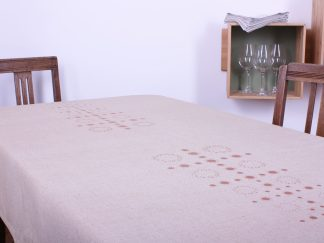 Die naturfarbene mittelgroße Tischdecke ist jeweils an den kurzen Seiten mit einem Muster verziert. Es entwickelt sich aus kleinen kreisförmigen Ornamenten zu einem Muster, das zum Ende hin immer breiter wird. Dadurch ergibt sich eine pyramidenähnliche Form. Das Design wurde mit Siebdruck handbedruckt. Die Tischdecke ist in dem Maß 180 mal 120 Zentimeter erhältlich.