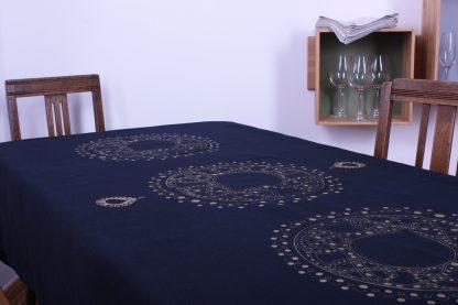 Das dunkelblaue Tischtuch in den Maßen 220 mal 130 Zentimeter ist das Highlight Ihrer schönen gedeckten Tafel. Es ist mit großen kreisförmigen Motiven in Gold handbedruckt. Zentral befindet sich ein großer Kreis, der von kleinen Punkten umrandet ist. Das Innere des Kreises ist auch gemustert. Der gleiche Kreis befindet sich ebenso links und rechts vom mittleren. Der mittlere Kreis wird zusätzlich oben und unten von zwei kleinen Tropfen flankiert. Alternativ gibt es die Tischdecke auch kleiner in 180 mal 120 Zentimeter.