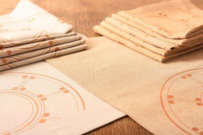 Das Bild zeigt zwei Serviettensets in zwei verschiedenen Sandtönen, sand und sand hell. Beide Serviettensets sind mit einem orientalisch inspirierten Motiv handbedruckt. Es zeigt einen verzierten Halbkreis in Bronze. Die Serviettensets umfassen je 6 Stück.