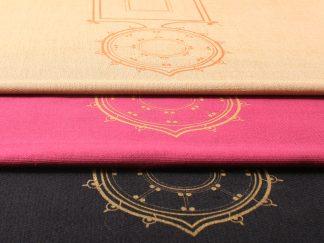 Das Bild zeigt das Sortiment der wunderschön verzierten Tischläufer von Mission Ornament. Sie liegen als Stapel übereinander. Es gibt sie in einem kräftigen pink, zartem Sandton oder einem warmen dunkelblau. Auf dem Foto erkennt man auch deutlich die Verzierung der Tischläufer. Die Verzierung ist orientalisch inspiriert, aber sehr klassisch und zeitlos gehalten. Es ist ein schmales Rechteck, das die längliche Form des Tischläufers wieder aufnimmt. Dem Rechteck ist an einer Seite ein spitzzulaufender Kreis angehängt. Das Motiv ist in Gold und Bronze auf die Stoffe im Siebdruckverfahren gedruckt worden.