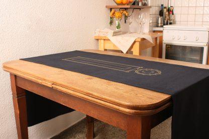 Das Foto ist ein schönes Beispiel dafür wie dekorativ ein Tischläufer sein kann. Das edle Wohnaccessoire liegt längst über dem 110 Zentimeter langen Tisch und hängt an beiden Seiten tief herunter. Der Tischläufer in dunkelblau ist mit einem Motiv in Gold handbedruckt, was einen schönen Kontrast zum warmen Dunkelblau darstellt. Den Tischläufer bietet Mission Ornament in verschiedenen Längen, je nach Ihren Bedürfnissen an.