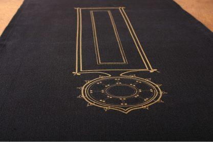 So dunkelblau wie Nacht ist der Tischläufer von Mission Ornament, der ausgebreitet auf einem Tisch liegt. Das goldfarbene Motiv, das das Textil ziert ist ornamental inspiriert und schafft einen schönen Kontrast zur Stofffarbe. Den Tischläufer gibt es in der Länge 180 und 220 Zentimeter.