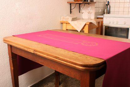 Hier sehen Sie die grandiose Wirkung, die ein schöner Tischläufer auf Ihrem Tisch haben kann. Der Tischläufer ist kräftig pink und 180 mal 50 Zentimeter lang ist. Die schöne Farbe passt perfekt zum Frühling und Sommer. Verziert ist der Tischläufer mit einem goldfarbenen handbedruckten länglichen Motiv. Das Rechteck trägt an einer Seite einen spitz zulaufenden Kreis.