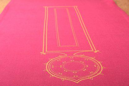 Auf dem Foto ist ein kräftig pinker Tischläufer in der Nahaufnahme zu sehen. Das Textil ist mit einem orientalischen Motiv in Gold handbedruckt. Es greift die längliche Form des Tischläufers auf und zeigt ein Rechteck, dem ein Kreis angehängt ist, der spitz zuläuft. Es gibt ihn in den Maßen 220 mal 50 und 180 mal 50 Zentimeter.