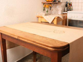 Das Bild zeigt einen sandfarbenen Tischläufer in der Größe von 180 mal 50 Zentimeter. Er liegt ausgebreitet auf einem Tisch. Der Tisch ist 110 Zentimeter lang und das Textil hängt an beiden Seiten je 35 Zentimeter über, was eine sehr schöne Wirkung ergibt. Das Textil ist mit einem dezenten orientalisch inspirierten Motiv in Bronze handbedruckt. Es greift die längliche Form des Tischläufers auf und zeigt ein Rechteck, dem ein Kreis angehängt ist, der spitz zuläuft. Das Foto ist ein wunderbares Beispiel dafür, welch schöne Dekorationswirkung ein Tischläufer hat.