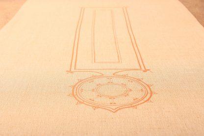 In der Nahaufnahme sieht man einen ausgebreiteten Tischläufer, der deutlich das zeitlos schöne Motiv in der Mitte des Textils zur Geltung bringt. Das mit Siebdruck gemachte Muster ist ein längliches Rechteck, das die Form des Läufers wiederspiegelt. An einem Ende ist ein verzierter angehängt der spitz zuläuft. Den Tischläufer gibt es in einem Sandton. Er misst 180 mal 50 Zentimeter.