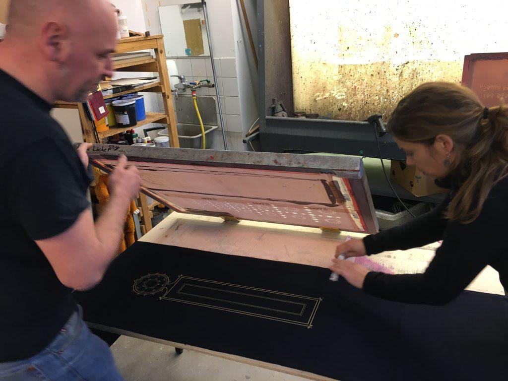 Das Foto zeigt Mathias Quast und mich, Stefanie Franke, bei der Arbeit in der Siebdruckdruckwerkstatt. Mathias ist mein Produktionspartner in Sachen Siebdruck.