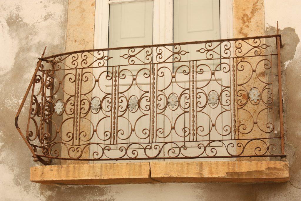 Das ornamentale Balkongitter, das auf dem Foto zu sehen ist, verziert einen kleinen Balkonvorsprung und schlichtes weiß gerahmtes Fenster. Das Bild entstand in Olhão in Portugal und soll zeigen, dass uns ornamentale Strukturen überall im Alltag begegnen.