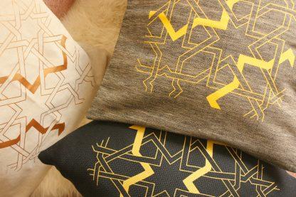 Auf dem Bild sieht man den bunten Dekokissen Mix von Mission Ornament. Es gibt drei Farben im Angebot: dunkelblau, grau und sand. Alle Kissen sind auf der Vorderseite handbedruckt. Das Motiv ist ein geometrisches orientalisches Flechtband.