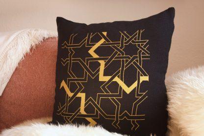 Das dunkelblaue Dekokissen von Mission Ornament ist mit einem geometrischen Flechtband in goldener Farbe auf der Vorderseite handbedruckt. Das Zierkissen ist zeitlos schön gestaltet und passt sich Ihrem Einrichtungsstil an. Hier liegt es auf einer roséfarbenen modernen Couch, umgeben von einer weißer Kuscheldecke und einem weißen Fell.