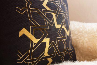 Das Foto verdeutlicht das harmonische Zusammenspiel mit dem dunkelblauen Halbleinen und dem goldfarbenen Druck des geometrischen Musters des Zierkissens von Mission Ornament.