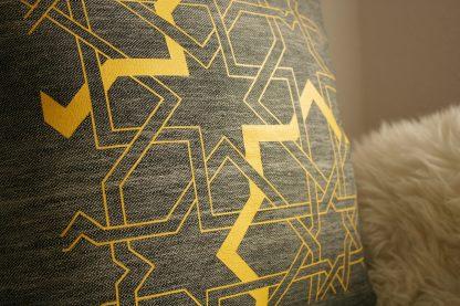 Die Abbildung zeigt in der Nahaufnahme den schönen hochwertigen Siebdruck des gelben Flechtbandes auf dem grauen Zierkissen von Mission Ornament.