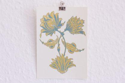 Hier sehen wir die Postkarte Pfingstrosenpaar in der Gesamtansicht. Die Grußkarte ist 10 mal 15 cm groß und besteht aus naturfarbenen Karton, der 300 Gramm schwer ist. Das Blumenmotiv füllt die ganze Fläche und zeigt zwei Pfingstrosen mit Blättern, deren Stängel sich bogenartig kreuzen. Das Pfingstrosenpaar wurde in gold und taubenblau im Siebdruckverfahren handgedruckt.
