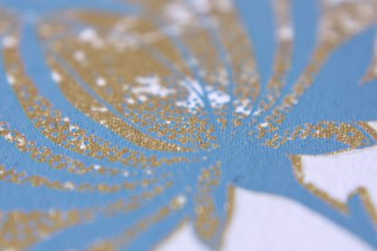 Das Foto zeigt den gold und taubenblauen Siebdruck des Blumenmotives von der Postkarte Pfingstrosenpaar in der Nahaufnahme.