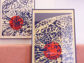 Die Abbildung zeigt die farblich unterschiedlichen Art Prints von Mission Ornament vergleichend nebeneinander. Die Art Prints wurden zwei beziehungsweise dreifarbig gestaltet. Bei der zweifarbigen Version wurde die ornamentale Gitterstruktur der Lampionblume in dunkelblau auf hellen Papiergrund gedruckt. Hinter der Gitterstruktur leuchtet die rote, rund abstrahierte Frucht durch. Bei der dreifarbigen Version wurde der Papiergrund zunächst golden vorgestrichen. Darüber liegt die invertierte Pflanzenstruktur in dunkelblau, wodurch man die rote Frucht leuchten sieht. Die Art Prints messen 35 mal 50 Zentimeter.